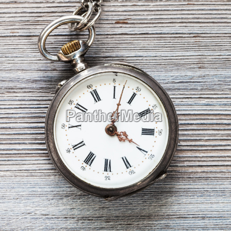 old pocket watch on gray wooden