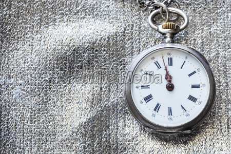 antique pocket watch on silver textile