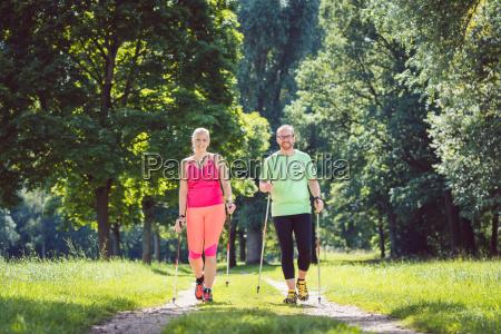 coppia che fa nordic walking per