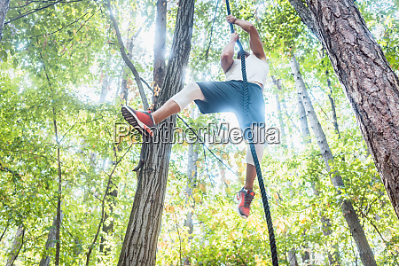 fit man climbing rope in outdoor