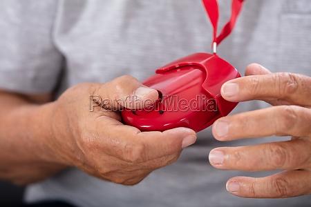 man holding personal alarm
