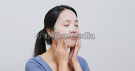 woman apply paper face mask at