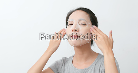 asian woman apply paper mask on