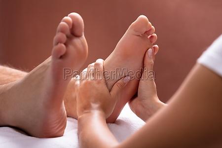 terapeuta dare massaggio piede alluomo