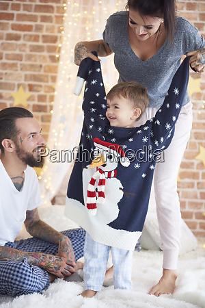 boy trying on oversized christmas sweater