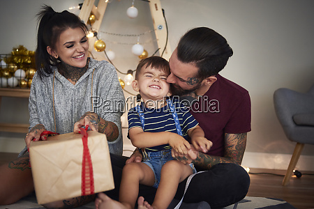 happy boy opening christmas present with