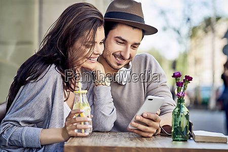 happy young couple looking at cell