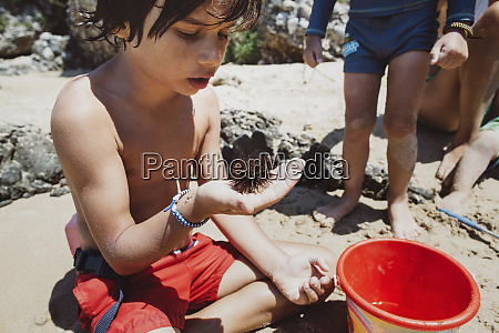boy sitting on beach looking at