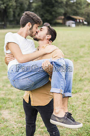 kissing young gay couple in a