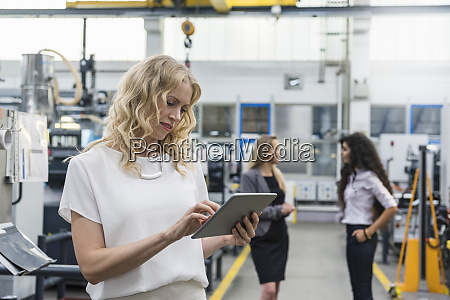 woman using tablet in factory shop