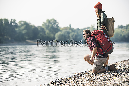 smiling young couple with backpacks at