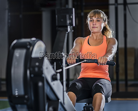 athletic young woman exercising with rowing