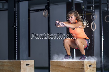 athletic young woman doing box jump