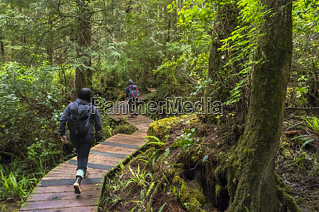 two people walk down a boardwalk