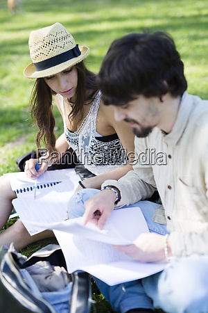 two students sitting on a meadow