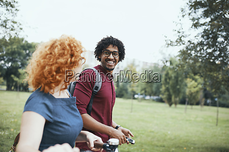 friends walking in park talking woman