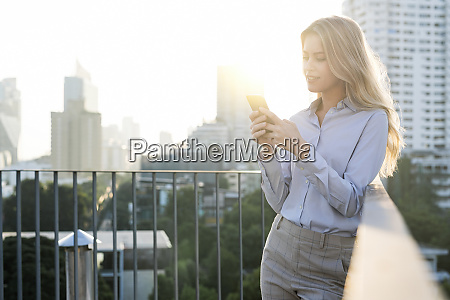 blonde business woman checking smartphone on