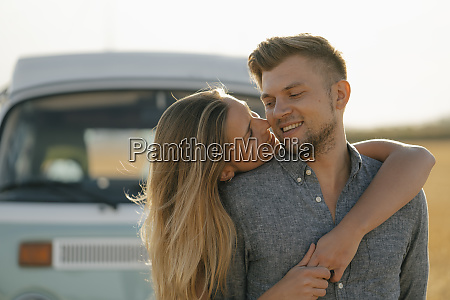 happy couple hugging at camper van