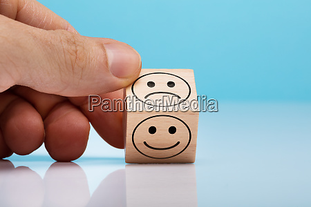 sad and happy face wooden block