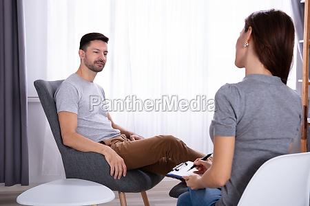uomo seduto sulla sedia vicino psicologo