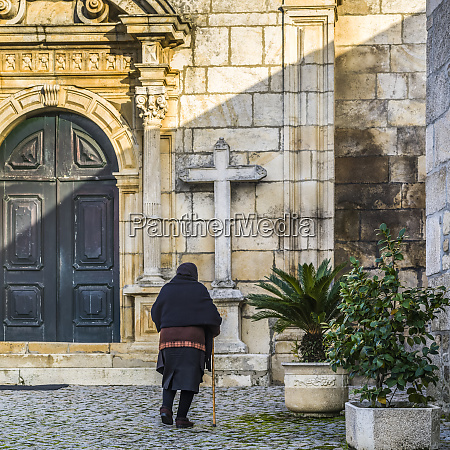 senior woman approaching a church lamego