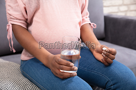 pregnant woman holding glass of water