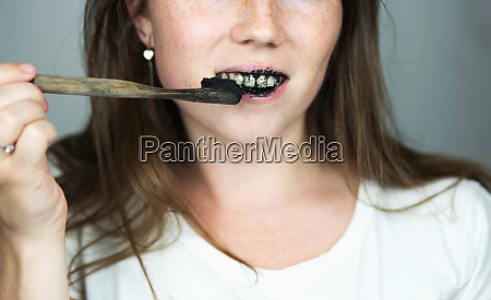 young woman brushing her teeth with