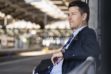 businessman waiting on station platform