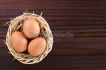 raw brown eggs on hay in