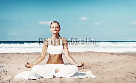 asana donna esercizio fisico spiaggia loto