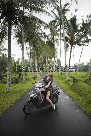 giovane donna in moto da palme