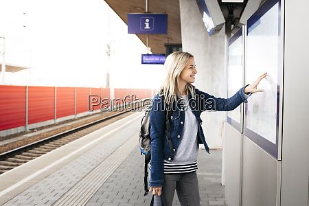 smiling woman checking the departures board