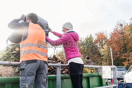 donna e uomo danno rifiuti verdi