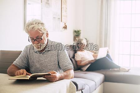 anziano uomo lettura libro come sua