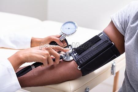 giovane medico che controlla la pressione