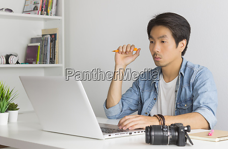 asian photographer or freelancer thinking in