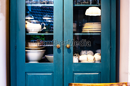 different white dishes in cupboard in