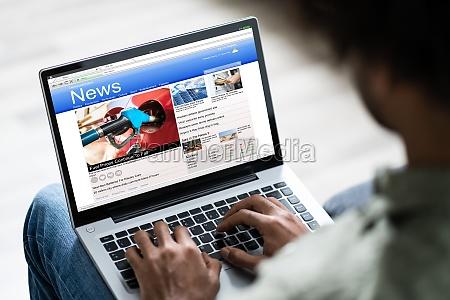 uomo guardando notizie online su laptop