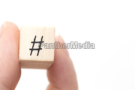 hand holding a wooden cube with