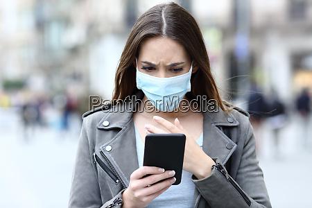 ragazza spaventata con maschera lettura notizie