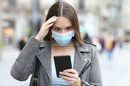 donna preoccupata con maschera controllo telefono
