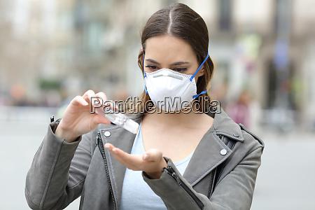 ragazza con maschera che applica disinfettante