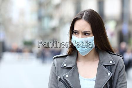 donna spaventata con maschera protettiva evitando