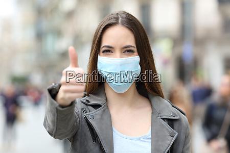 donna felice con maschera gesticolante pollici
