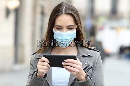 donna con maschera guardando il video