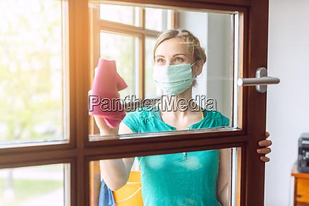 donna pulizia finestre durante covid 19