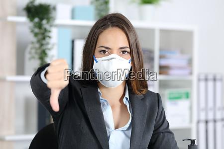 esecutivo con maschera gesticolante pollici verso