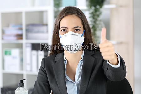 esecutivo con maschera con pollici in
