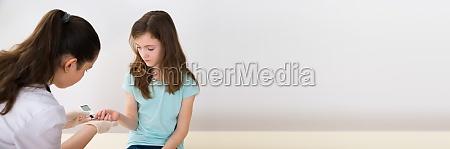 doctor measuring blood sugar level of