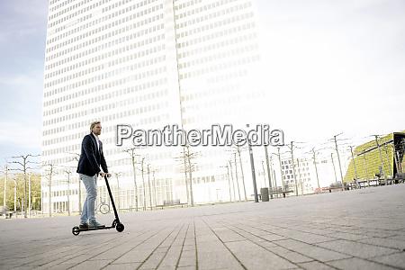 imprenditore in sella a kick scooter